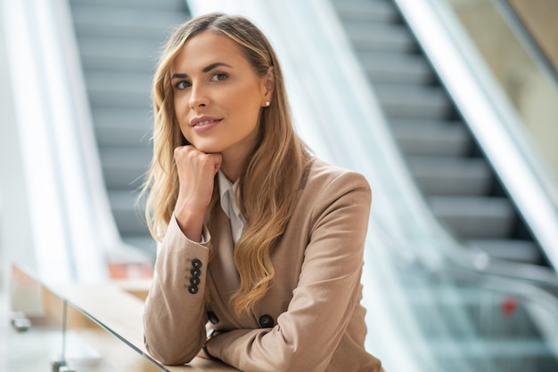 Femme d'affaires en attente et en pensant près d'un escalator