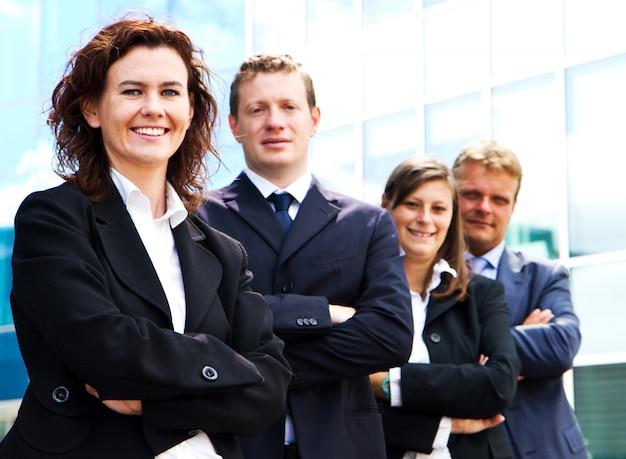 Femme d'affaires attrayant avec les bras croisés, debout devant des collègues