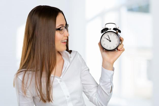 Femme d'affaires attrayant tenant réveil