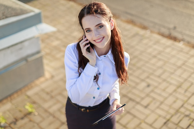 Femme d'affaires attrayante en blouse blanche et jupe noire, debout sur le toit et parlant au téléphone