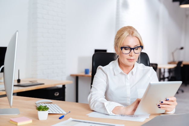 Femme d'affaires attrayante mature travaillant au bureau avec tablette pc