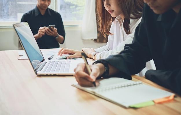 Femme d'affaires au bureau en chemise décontractée. sélection d'informations avec des collègues.