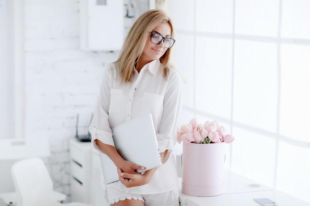 Femme d'affaires au bureau dans de beaux vêtements avec un ordinateur portable dans ses mains à côté d'un bouquet de fleurs