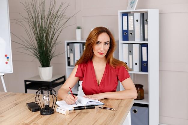 Femme d'affaires au bureau dans le bureau écrit dans un cahier