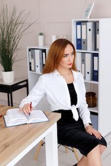 Femme d'affaires au bureau dans le bureau mange dans un cahier de papier