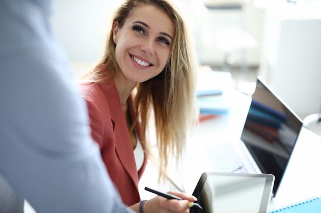 Femme d'affaires au bureau met une signature électronique sur tablette