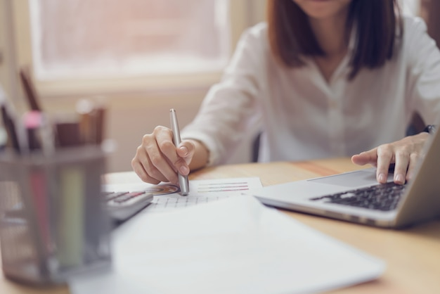 Femme d'affaires au bureau et utilise un ordinateur et une calculatrice pour effectuer la comptabilité financière.