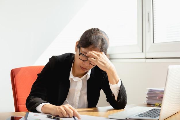 Femme d'affaires au repos les mains sur la tête avec les yeux au bureau de travail au bureau.