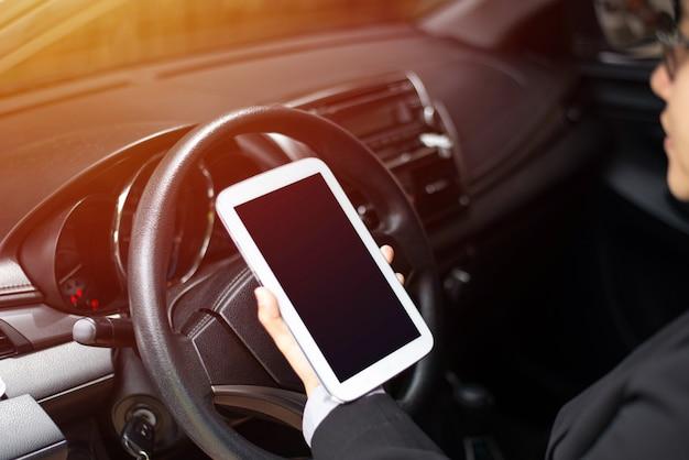 Femme d'affaires au volant et à l'aide d'une tablette, concept de technologie de communication