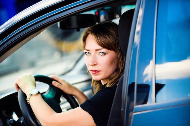 Femme d'affaires au volant de sa voiture.