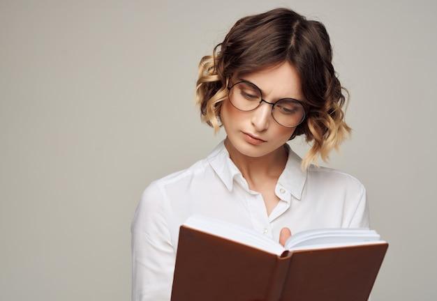 Femme d'affaires aux cheveux bouclés portant des lunettes livre exécutif professionnel