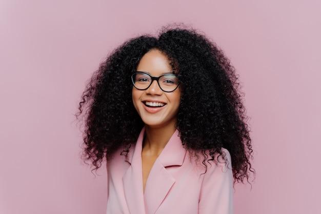 Femme d'affaires aux cheveux bouclés positive porte des lunettes