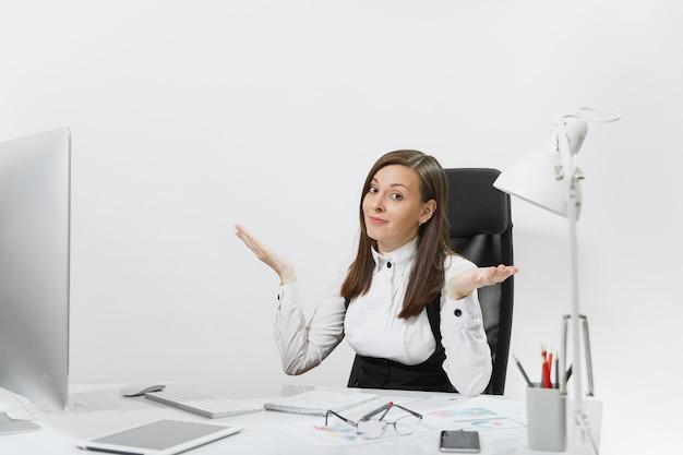 Femme d'affaires aux cheveux bruns perplexe et absorbée en costume et lunettes assise au bureau, travaillant à l'ordinateur avec un moniteur moderne avec des documents dans un bureau léger, écartant les mains