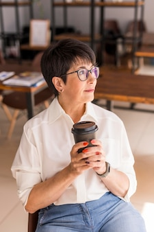 Femme d'affaires aux cheveux courts tenant le café et à l'écart
