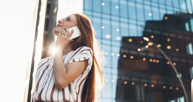 Femme d'affaires aux cheveux rouges du caucase avec des taches de rousseur parle au téléphone tout en regardant loin à travers des lunettes