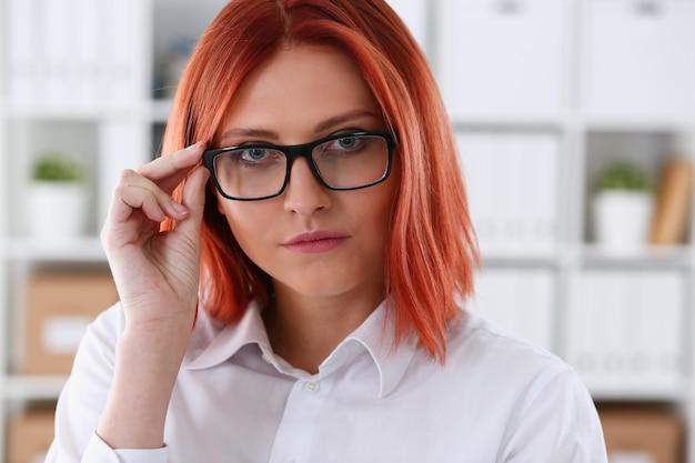 Femme d'affaires aux cheveux rouges avec des lunettes