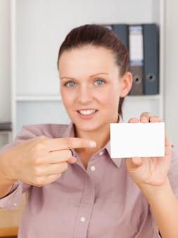 Femme d'affaires aux cheveux roux pointant sur une carte