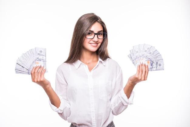 Femme d'affaires aux longs cheveux bruns en vêtements blancs détiennent beaucoup de billets en dollars sur blanc