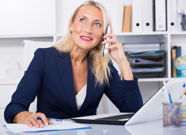 Femme d'affaires ayant une conversation téléphonique au bureau