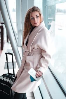 Femme d'affaires avec des bagages pose à l'aéroport.