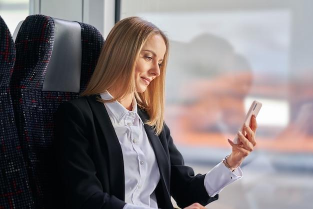 Femme d'affaires de banlieue dans les transports publics à l'aide d'un smartphone