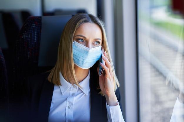 Femme d'affaires de banlieue de métro dans le masque sur les transports publics à l'aide de smartphone