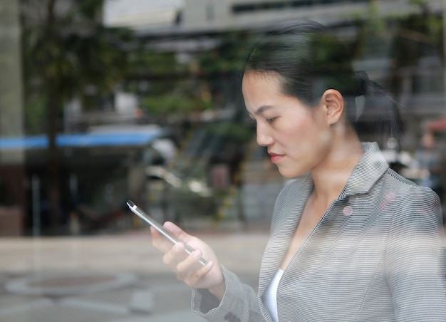 Femme d'affaires belle à l'aide d'un smartphone au verre de réflexion de l'immeuble de bureaux.
