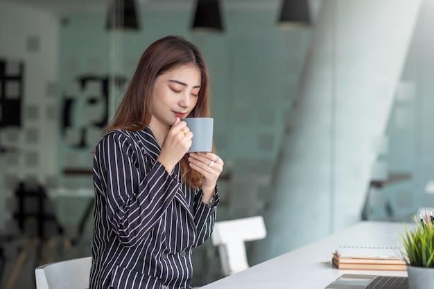 Femme d'affaires belle asiatique, boire du café assis au bureau
