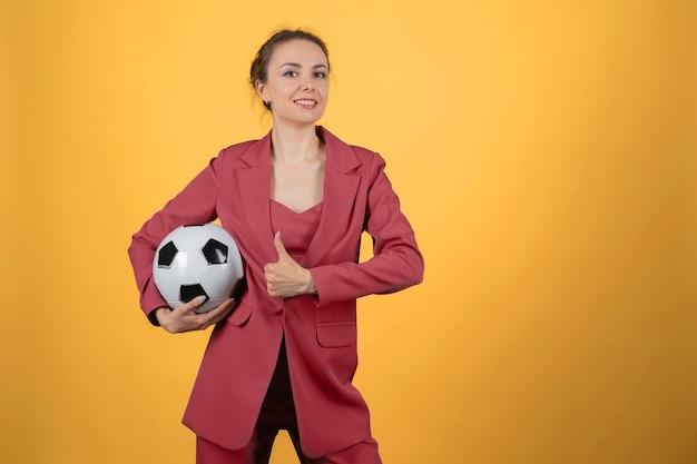 Femme d'affaires de belle jeune femme avec ballon de football posant sur fond jaune. montrant le pouce vers le haut