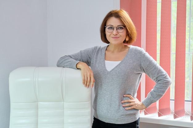 Femme d'affaires belle mature avec des lunettes, pull en cachemire près de fauteuil de bureau en cuir blanc