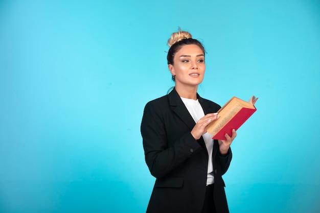 Femme d'affaires en blazer noir avec un livre rouge.