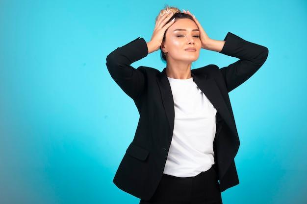 Femme d'affaires en blazer noir tenant sa tête.