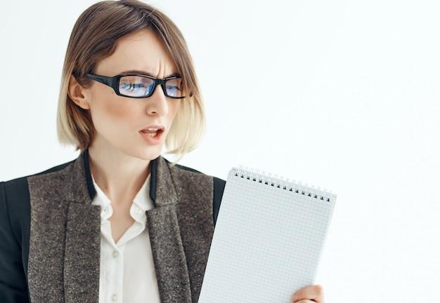 Femme d'affaires avec le bloc-notes dans l'espace de copie de fond clair de bureau de mains