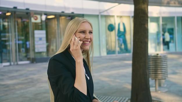 Femme d'affaires blonde adulte en costume assis sur un banc.