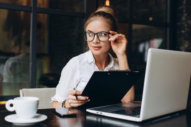 Femme d'affaires blonde assise sur un espace de travail et utilisant un ordinateur portable au bureau, elle regarde un dossier contenant des documents, discutant par téléphone et buvant une tasse de café.