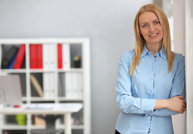 Femme d'affaires blonde au bureau avec espace de copie. caméra souriante et regardant.