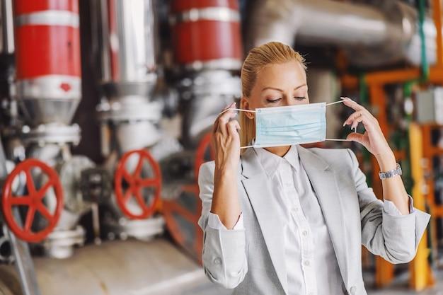 Femme d'affaires blonde en costume mettant un masque facial en se tenant debout dans son usine pendant le virus corona.