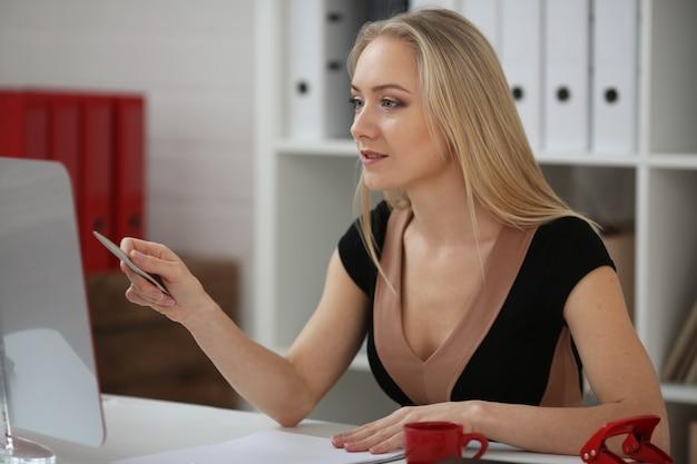 Femme d'affaires blonde est engagée dans l'éducation: regarde attentivement le moniteur à l'aide d'un stylo comme un pointeur