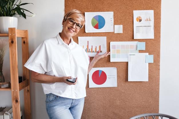 Femme d'affaires blonde montre des graphiques à bord