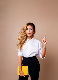 Femme d'affaires blonde pointant vers le haut et à la recherche sur le mur beige. porter des vêtements de travail élégants. copiez l'espace pour le texte. visage surprise.