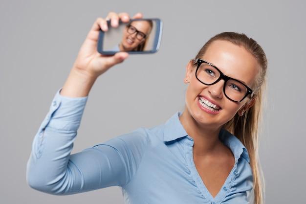 Femme d'affaires blonde portant des lunettes prenant photo autoportrait