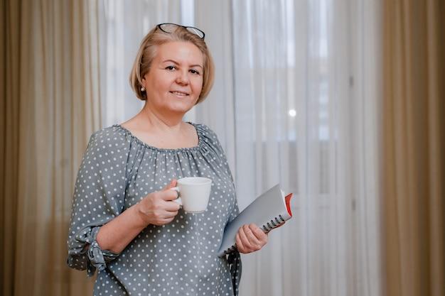 Femme d'affaires blonde, souriante et âgée, portant des lunettes avec une tasse et un journal de tablette.
