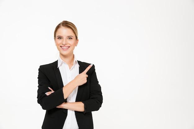 Femme d'affaires blonde souriante pointant loin sur blanc