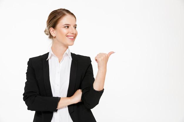 Femme d'affaires blonde souriante regardant et pointant loin sur blanc