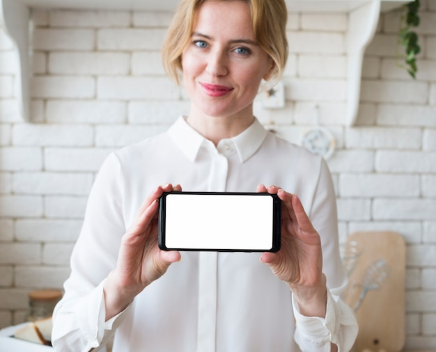 Femme d'affaires blonde tenant un smartphone avec écran blanc