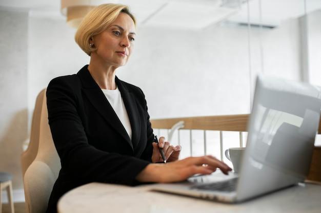 Femme d'affaires blonde travaillant sur son ordinateur portable