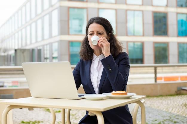 Femme affaires, boire, café, utilisation, ordinateur portable