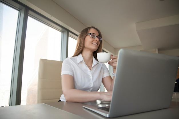 Femme d'affaires, boire du café au bureau