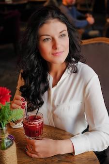Femme d'affaires boit du vin chaud dans le restaurant.