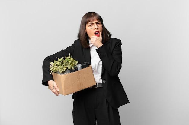 Femme d'affaires avec la bouche et les yeux grands ouverts et la main sur le menton, se sentant désagréablement choquée, disant quoi ou wow